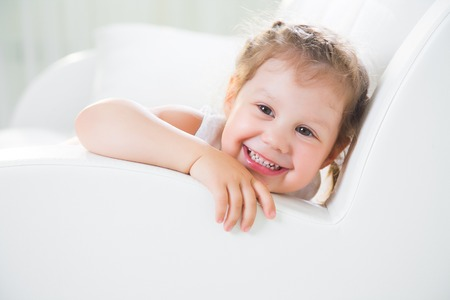 1 person: Portrait of little girl on white sofa at home