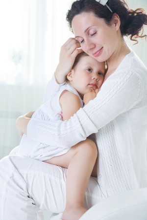 Mom hugs a crying little daughter at home Stock Photo