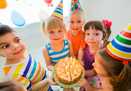 group of children at birthday party with cake photo