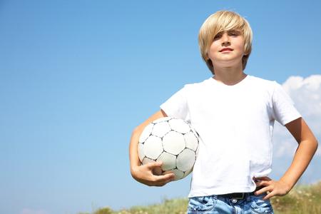 futbol infantil: Retrato de muchachos adolescentes lindos con balón de fútbol contra el cielo azul