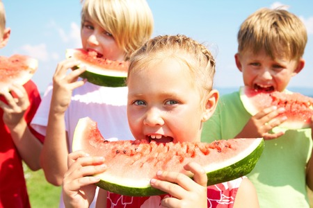 Children eating red watermelon on blue sky background photo