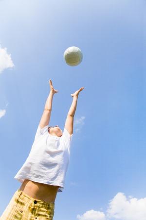 futbol infantil: pequeño jugador de fútbol saltar por el balón contra el cielo azul Foto de archivo