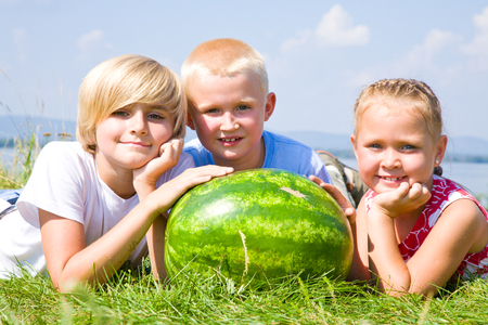 Children with  watermelon lying in green drass on blue sky background photo