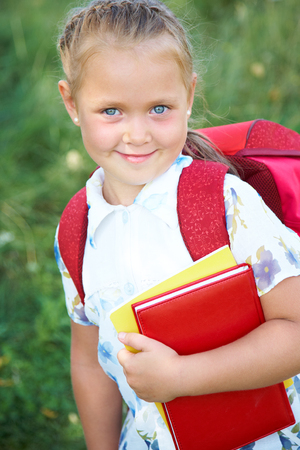 Portrait of cute girl with red backpack and books photo