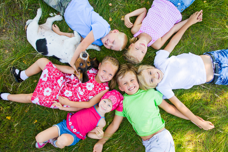 Six  cute children playing wiyh dog  in green grass at summertime