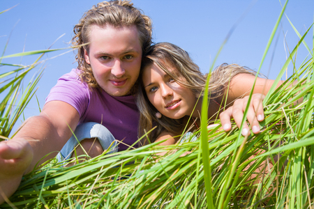 Young attractive couple relaxing in the grass