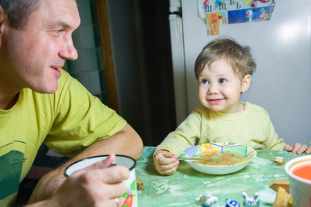 Father with a small daughter eats in the kitchen Stock Photo