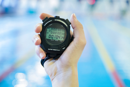 hand  with a stopwatch during competitions in the swimming pool Stock Photo