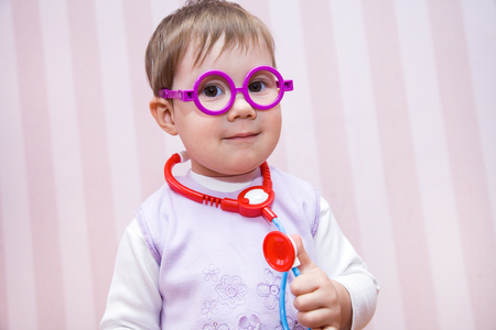 1: Little girl child plays at doctor Stock Photo