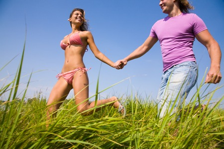 family health: Young attractive couple runs on the green meadow