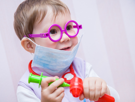 Little girl child plays at doctor Stock Photo