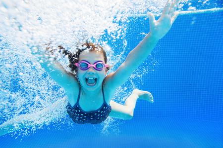 actividades recreativas: niña crea burbujas bajo el agua en la piscina