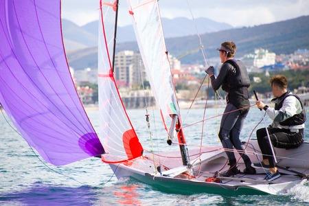 Couple of young guys drives a sailing yacht on the sea