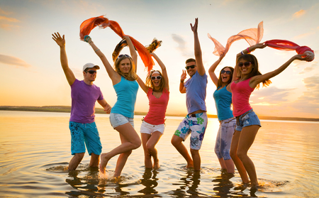 Young fun people enjoying summer on the beach at sunset