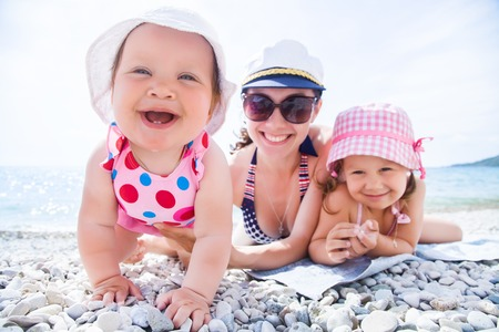 carrying: Young mother with little children playing on the beach in swimsuit Stock Photo
