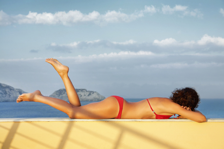 Beautiful slim  girl sunning on seacoast photo