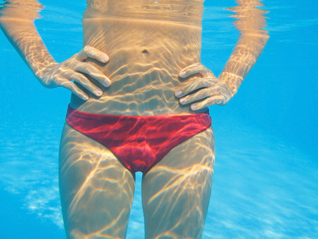 part of the body beautiful slender woman under water in the pool photo