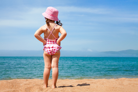 little girl in a swimming suit looks at the sea photo