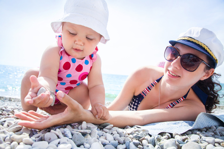 resort life: Young mother with little children playing on the beach in swimsuit Stock Photo