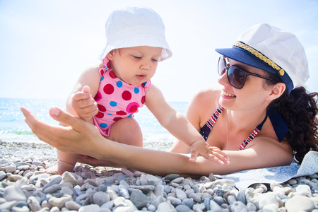 Young mother with little children playing on the beach in swimsuit Stock Photo