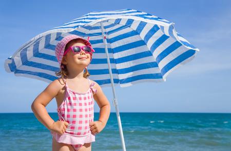 Gelukkig meisje aan de kust onder een paraplu in de zomer Stockfoto