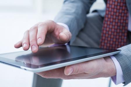 Unrecognizable business man holding a digital tablet photo