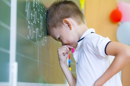 study: Schoolboy standing near blackboard with formula Stock Photo