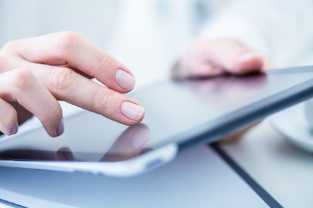 working office: Close-up of female hands touching digital tablet Stock Photo