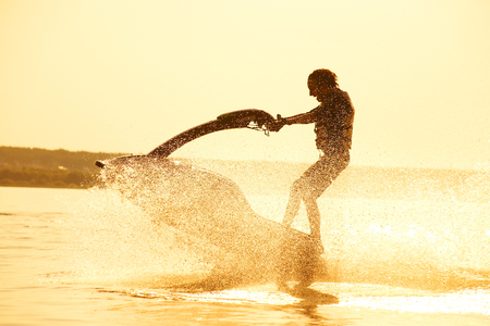 jet skier: strong man drive on the jetski above the water at sunset .silhouette. spray. Stock Photo
