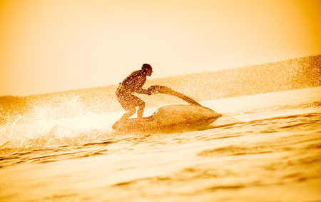 young man drive on the jetski above the water at sunset .silhouette. spray. Stock Photo
