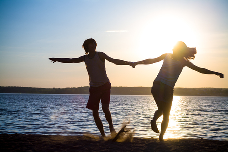 afecto: Young lovers happily spend time at sunset on the beach