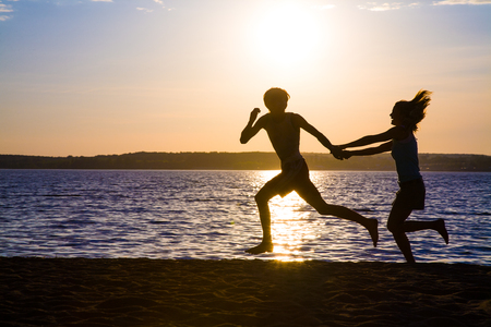 Young couple in love running at sunset on the beach