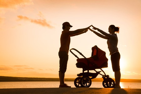 Silhouettes of parents protect their child in a stroller Stock Photo
