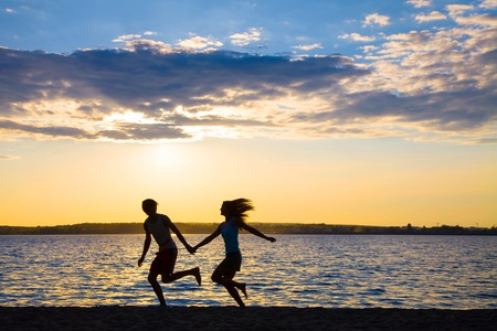 Young couple in love running at sunset on the beach photo