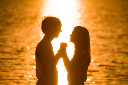 Young lovers happily spend time at sunset on the beach photo