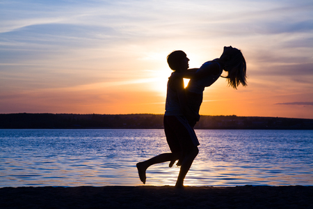 Young lovers happily spend time together at sunset on the beach photo