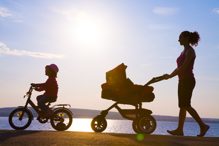 Silhouettes of parents walk with small children with a stroller photo