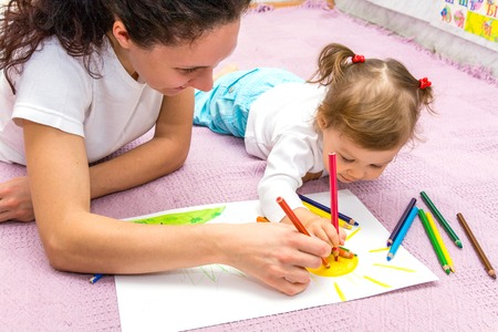 mother draws with a small daughter lying on a floor Stock Photo