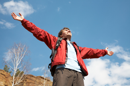 Happy man hiker holding his arms in the air in a feeling of success having reached the summit Stock Photo