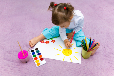 The small beautiful girl paints on a paper Stock Photo