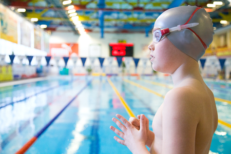 young swimmer stands on the side of the pool photo