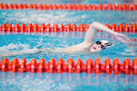 The young swimmer swims along the path of the pool photo