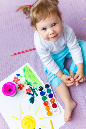 paints: Portrait of  small beautiful girl paints on a paper Stock Photo