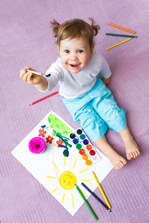 paper sheet: Portrait of  small beautiful girl paints on a paper Stock Photo