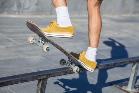 skateboarders feet while skating on concrete at the skate park