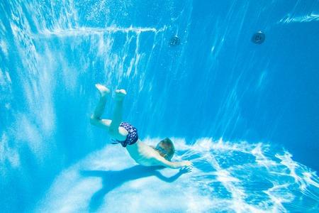 actividades recreativas: Foto submarina de niño nadando en la piscina