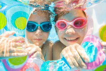 underwater photo of  little kids  swimming  in pool
