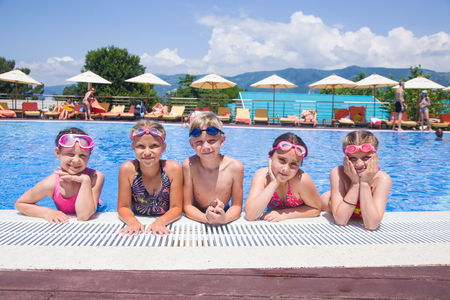 Group of rkids swimming in pool on resort