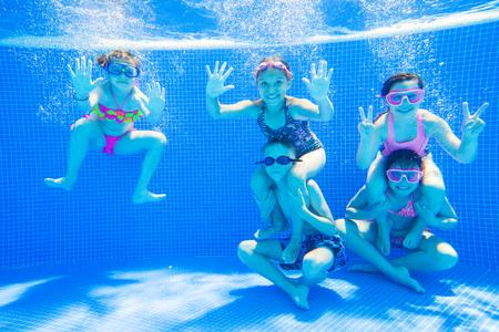 actividades recreativas: Niños pequeños nadando en la piscina bajo el agua.