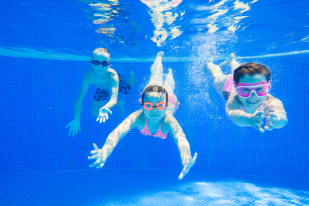 little kids swimming  in pool  underwater.